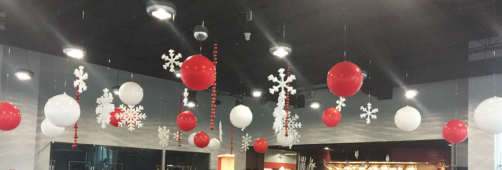 A ceiling decorated with suspended white and red 30 inch diameter balloons and snowflakes
