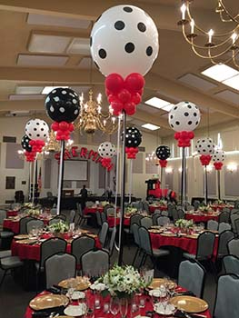 These heilum filled 30 inch polka dot covered black and white centerpiece balloons are each adorned with red collar balloons.  They float 5 feet over each table anchored to a floral arrangement on each table.