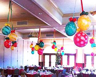 Clusters of Balloonatics 24 inch diameter Christmas decoration balls are encased in clear long-lasting mylar balloons and serve as an excellent holiday party ceiling decoration