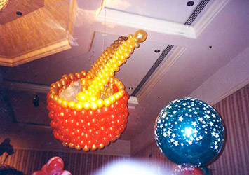 This five foot balloon toy drum is suspended from the ceiling of a Fairmont Hotel ball room for a toyland theme holiday party where guests were surrounded by toys as big as themselves