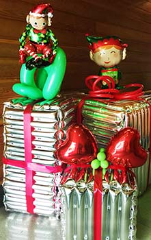 A pair of four-foot tall balloon sculpture elves playing in the gift packages awaiting delivery