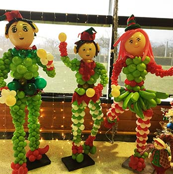 A trio of three five-foot tall balloon sculpture elves for a Santa's workshop venue