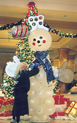 This eight foot tall snowman sculpture has personality and style with foamcor hat and mittens, and serves as a major focal decor piece for a holiday party.