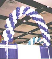 Swirled balloon arches over a trade show booth improve regonition