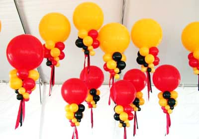 Giant 30 inch red and goldenrod helium filled balloons with tiered collar balloons placed to visually unify decor in a large tent venue