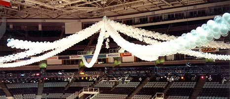 Garlands of white, clear and silver latex balloons spaning the San Jose, Ca. arena in spoke-like pattern to create the perception of a giant tent for guests at a corporate event on the arena floor.