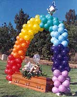 This packed style balloon arch in the colors of the rainbow was part of a grave side memorial service
