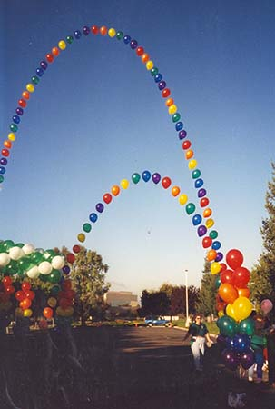 This 40 foot tall string-of-pearls style balloon arch is constructed in rainbow colors from equally spaced single balloons to visually carry the eye skyward.