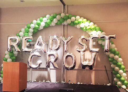 A spiral packed 30 foot balloon arch with mylar lettrs expressing the theme of a corporate meeting