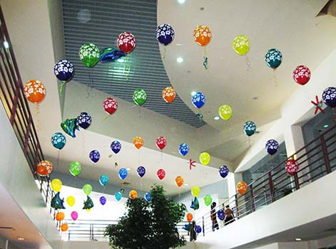 A series of multicolored helium filled string-of-pearls style balloon arches span the atrium in this corporate location for a corporate employee event.