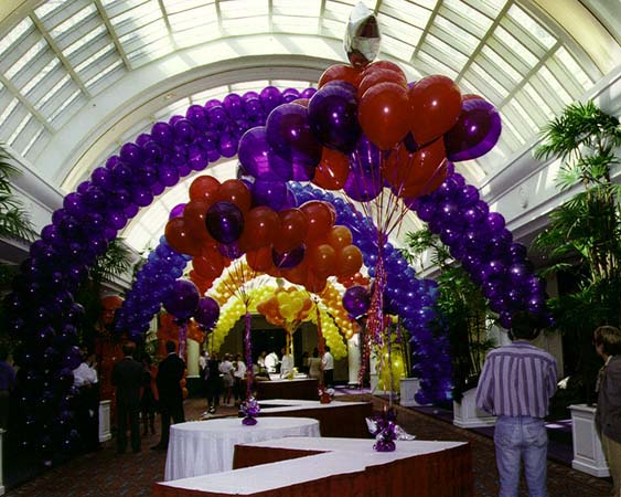 This series of packed balloon arches in vivid magenta and citrine yellow colors are placed to decorate a long concourse hall between two event venues forming a visual tunnel focusing attention on the displays placed in the hall.