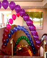 These string-of-pearls syyle balloon arches float over an escalator at the San Jose Fairmont Hotel to provide a visual pathway leadin g guests to an event in the ballrooms