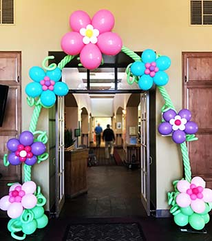 A playful entrance arch created of balloon fantasy flowers on a balloon vine.