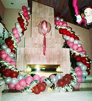 Garlands of silver, pink and burgundy balloons flank the fireplace in a private residence.