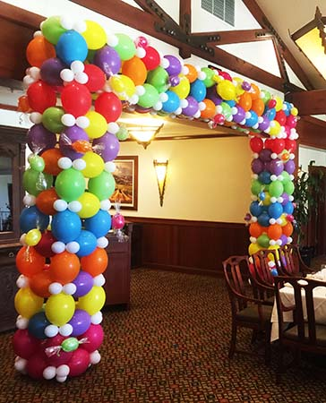 This squar cornered packed style balloon entrance decoration in vivid jelly bean colors is placed to frame the room entrance to a light hearted celebration event venue.