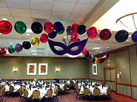 Garlands of 18 inch red, emerald green, gold and blue shiny mylar balloons radiate out from the center of the ceiling to decorate this Mardi Gras-themed event.