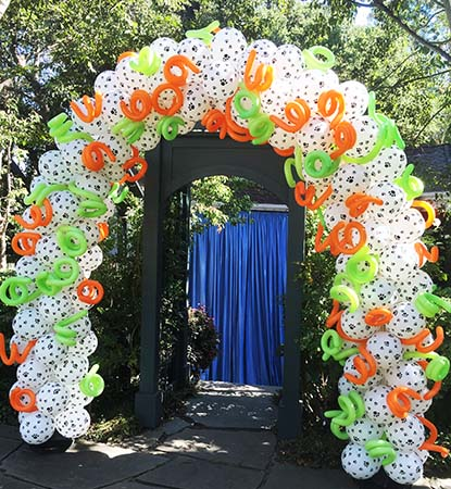 This white packed balloon arch is covered with imprinted paw prints for a pet lover party.