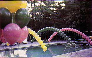 Balloon arches float over a swimming pool as part of the decroation for a yard party