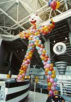 This giant 30 foot tall carnival fun house style balloon clown is sculpted from of a variety of orange, yellow, red, and light blue balloons giving its legs, body and arms the look of a circus clown.  The 5 foot diameter head is adorned with a red nose, large smiling mouth and sideburns.  It is placed to set the theme to a corporate circus theme party so that guests to this event at the San Jose SAP arena must walk thru his legs to enter.