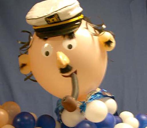 A six foot tall caricature-style balloon sculpture of a crusty old seaman in seaman's hat enjoying his balloon pipe for a sea theme party