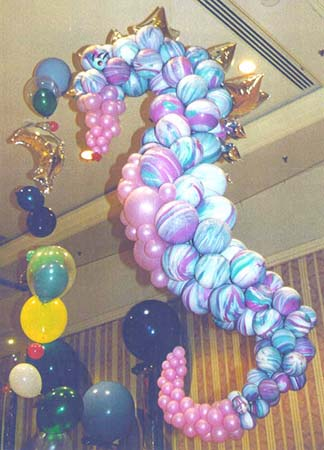 A five foot tall balloon sculpture of a seahorse created from agate and rose colored balloonswith gold mylar balloons for a mane is suspended from the ceiling as one of the decorations at an  under the sea theme party