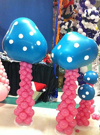 Our five foot tall balloon sculpture Magic Mushrooms are created with rose colored stems topped by double-stuffed blue polka dot balloons