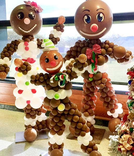 Six foot tall balloon sculptures of Mom, Pop, and Jr Gingerbread