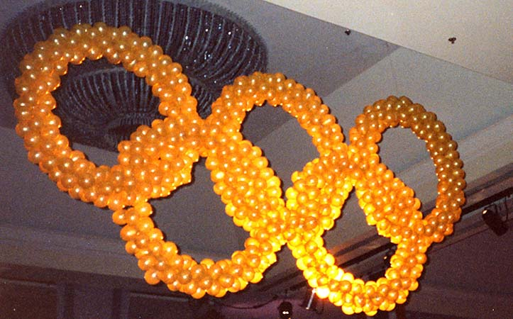 This balloon sculpture of the Olympic Rings is made from four foot diamater circles of clear balloons mounted over strand lighting.  This Olympic rings balloon sculpture is suspended from the ceiling of a hotel ballroom for a corporate olympics celebration event.