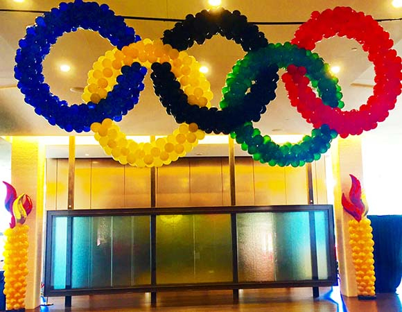 This balloon sculpture of the Rio Olympic Rings is made from four foot diamater circles of ring color balloons mounted as an event entrance piece.