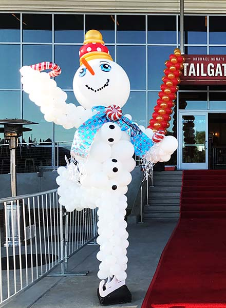 A six foot tall balloon sculpture of a giant snowman on figure skates