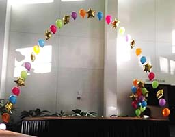 String-of-Pearls style balloon arch interspersed with mylar star balloons for a celebration event