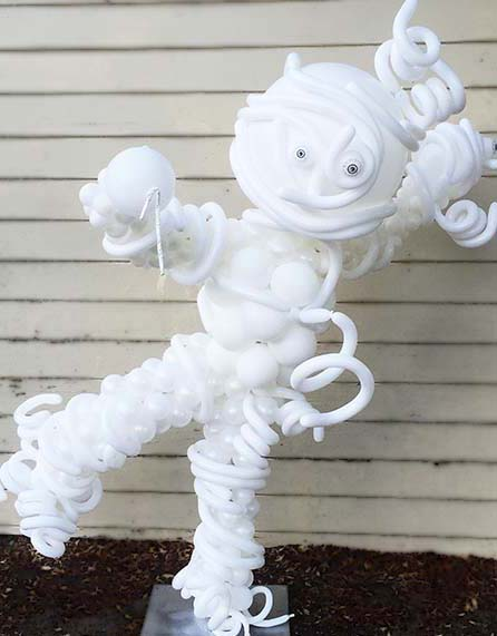 A five foot tall balloon mymmy sculpture dripping its mummy wrapings all in ghostly white