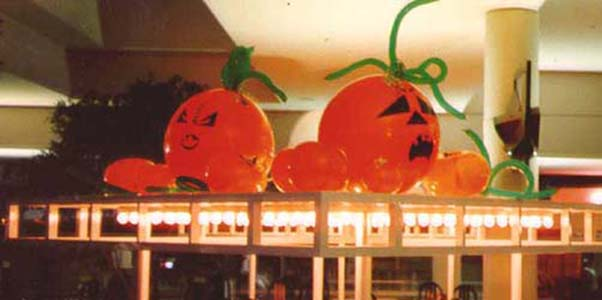 A series of orange 30 inch diameter pumpkin balloons with green vine accents arranged on an elevated surface as a pumpkin patch.