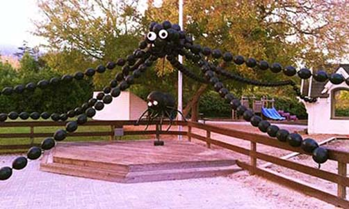 This giant balloon spider sculpture decorates an outdoor play area for a Halloween event.