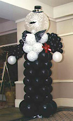 An eight foot tall formal balloon greeter figure of black and white balloons.