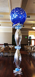 This bubble decoration made of silver mylar vertical balloons with pale blue balloon collars is topped by a large saphire blue balloon with snow flake designs