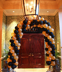 A swirled arch of gold and black balloons frames the entrance to this restaurant with a look of elegance.