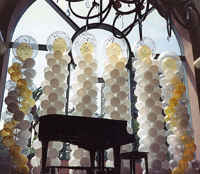 These ten foot tall swirled columns of white, clear, and gold provide an elegant background decoration for this grand piano