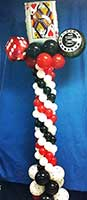 A red, white and black balloon column topped by a giant playing card and dice balloons serves as an area decoration for casino theme events