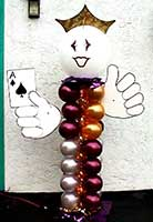 A 7 foot tall balloon column greeter figure of gold and magenta balloons topped by a white