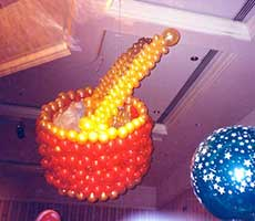 Balloon sculpture of a giant toy drum complete with drumsticks suspended from the ceiling