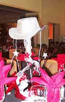 A sparkling silver colored centerpiece consisting of a six gun and western hat for a western theme event