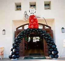 A giant two-story tall cowboy balloon sculpture with his bow legs stradling the entrance doors to a wewtern theme event