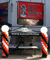 Balloon columns in team colors flanking an information table for a Giants baseball event