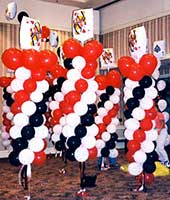 Seven-foot tall columns of swirled red, white and black latex balloons topped by playing card mylar balloons for a casino theme event