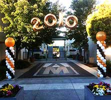 Columns of swirled white, gold, and black balloons topped by giant gold balloons flank the entrance driveway and anchor an arch suspended over the drive for a New Year event